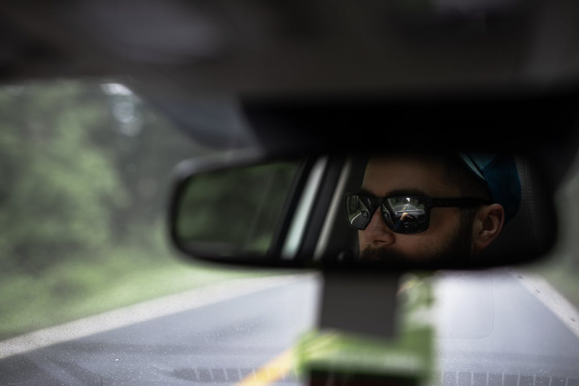 Reflection Of A Man On Rear View Mirror