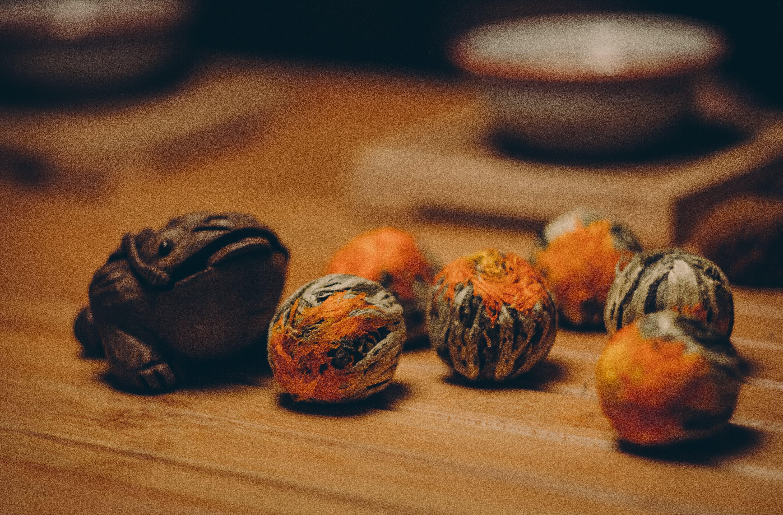 Brown Frog Figurine Beside Orange and Gray Fruits