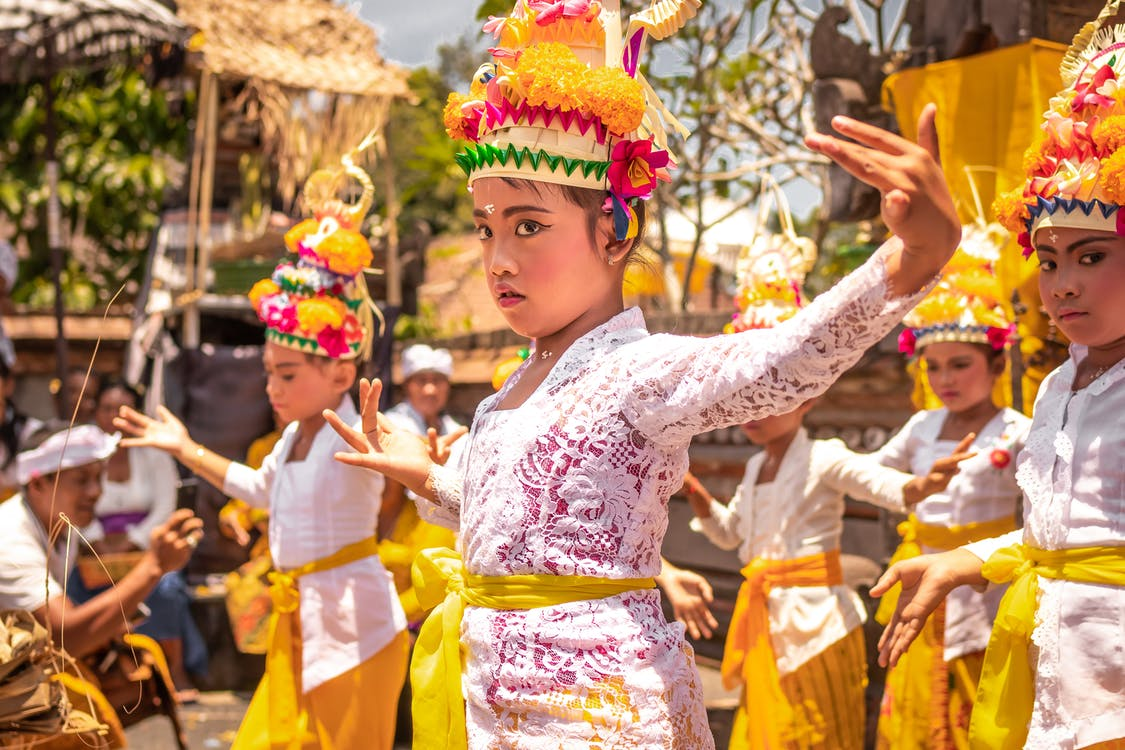Children Wearing Yellow and White Traditional Costumes and Dancing