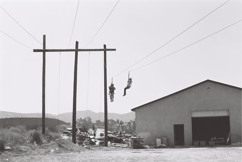 Two Persons Working On Electric Cables Near Building