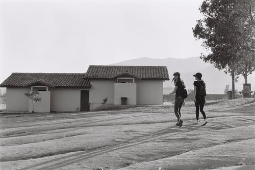 Two Women Walking Near House