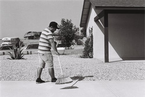 Grayscale Photo of Man Sweeping Driveway
