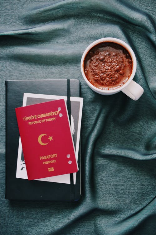 White Ceramic Mug and a passport and a book