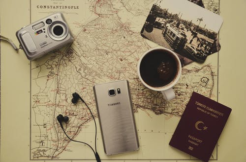 Silver Camera Near Black Coffee in Mug, Silver Samsung Galaxy S7, Turkey Passport, and Black Earbuds