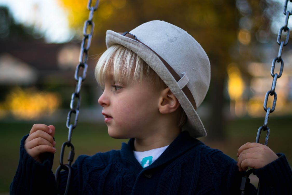 Kid in Gray Round Hat on Hanging Swing