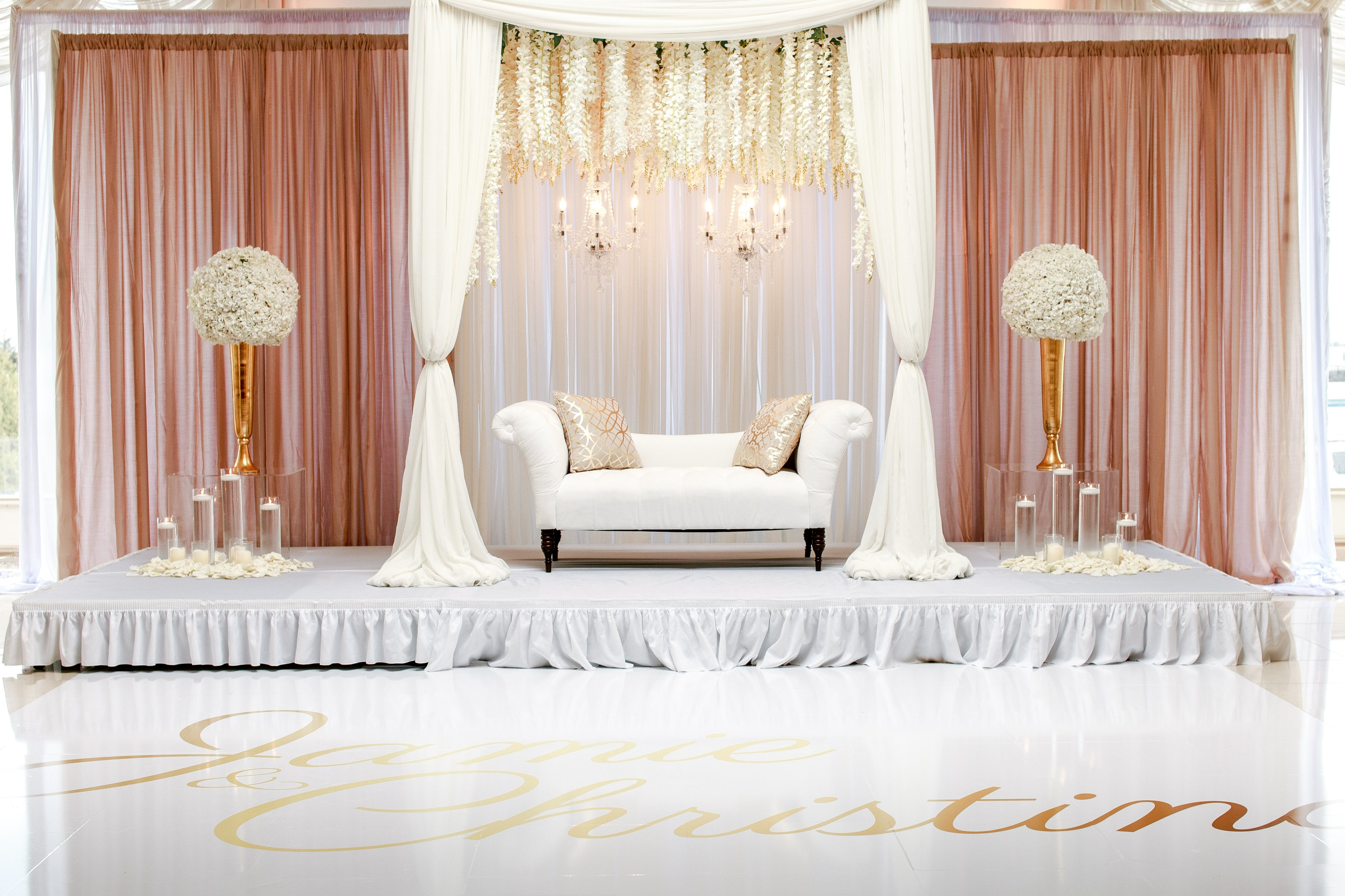 White Fabric Loveseat With Two Flower Centerpieces on the Side