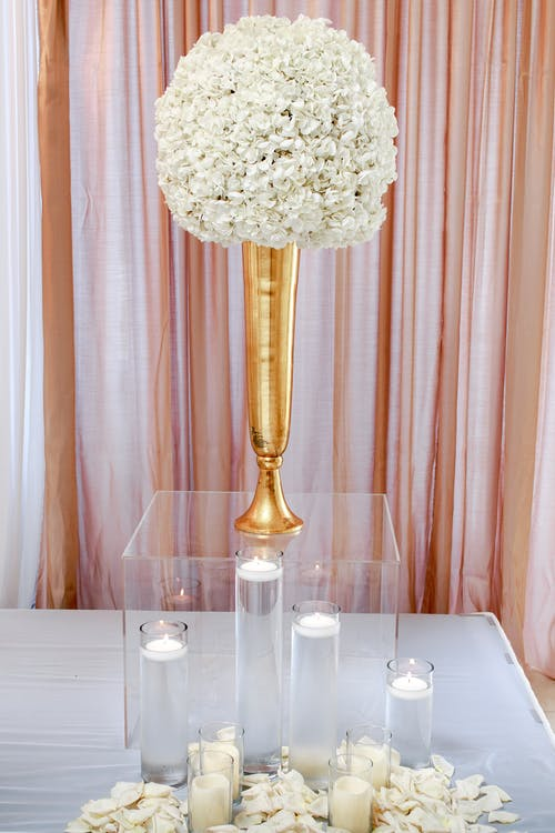 White Flower Centerpiece on Clear Glass Box With Candles