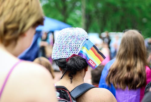 Selective Focus Photography of Woman With Lgbt Flaglet on Her Hair