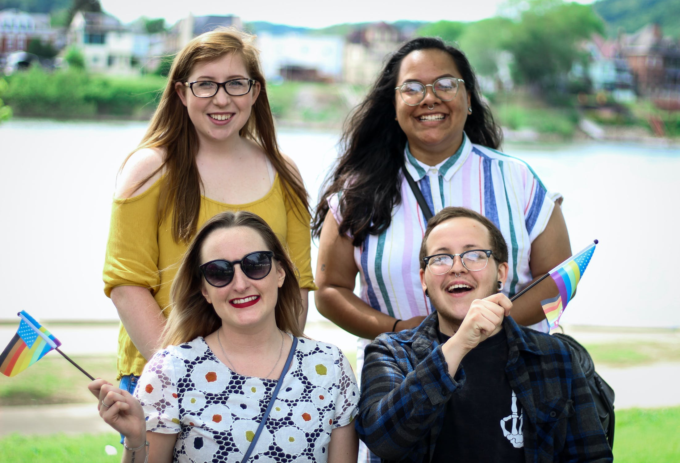 Four friends posing in two levels for a smiling portrait in a park. Two of the friends are holding rainbow pride flags.