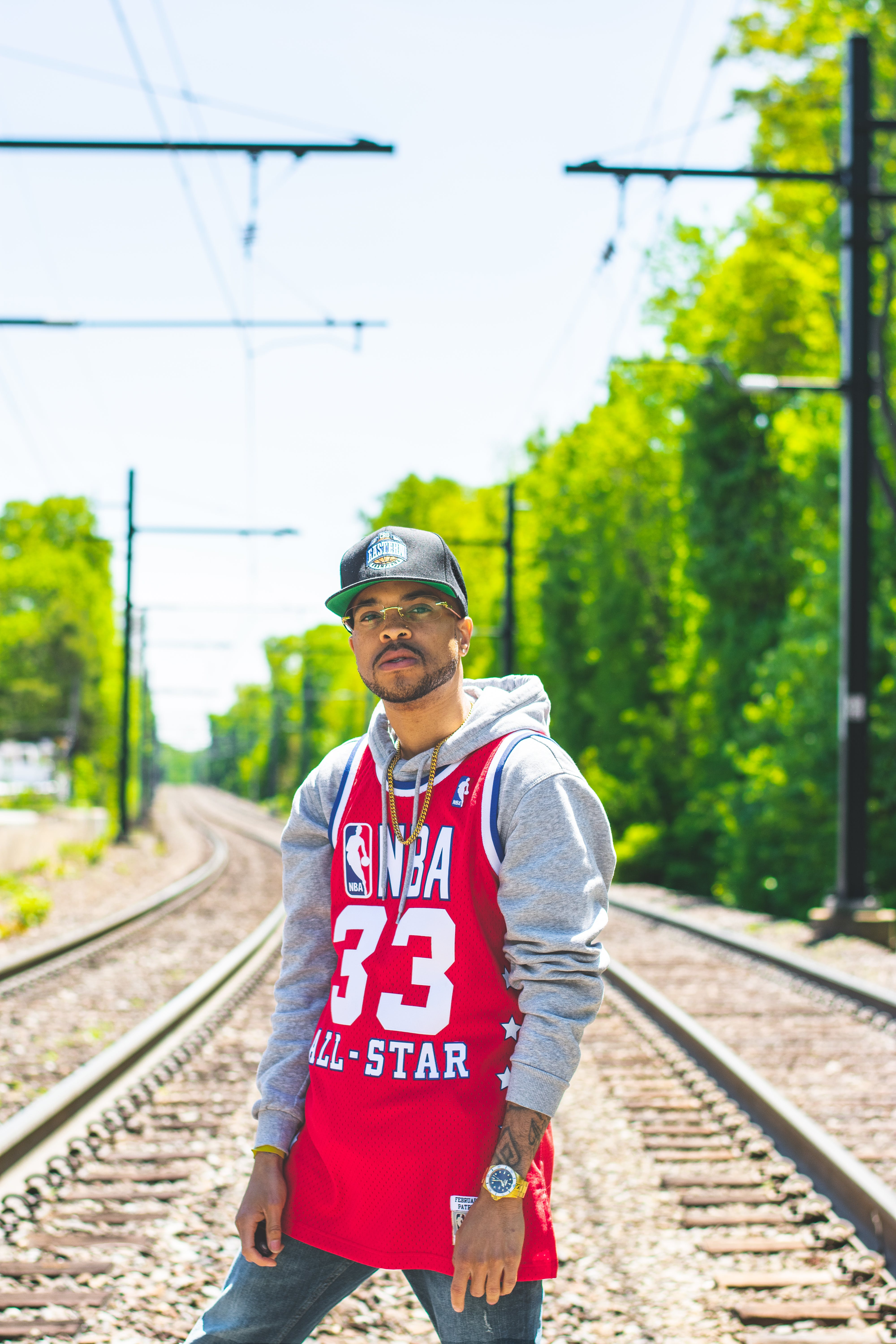 Man in Red and Gray Pullover Hoodie Standing on Train Tracks