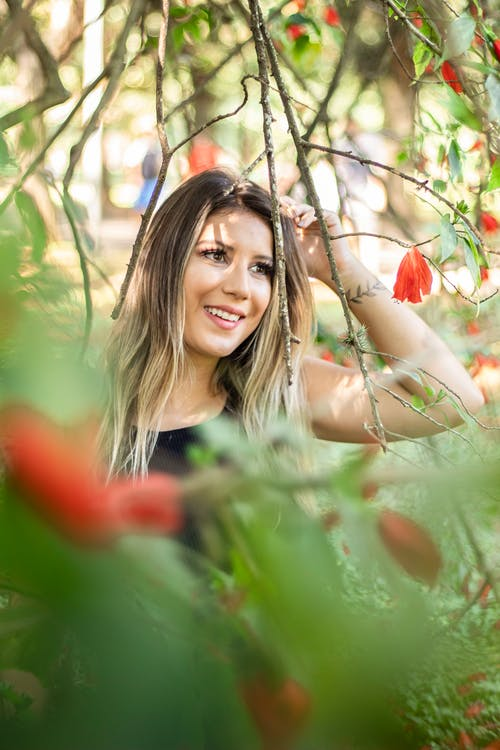 Smiling Woman Standing Under Red Flowered Tree