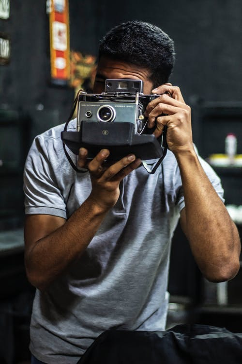 Man Holding Gray and Black Camera Inside Well Lit Room
