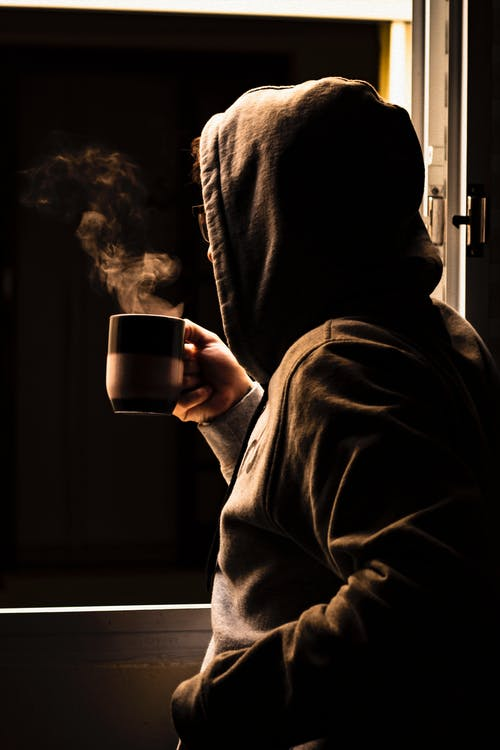 Person Drinking Coffee Next to Window