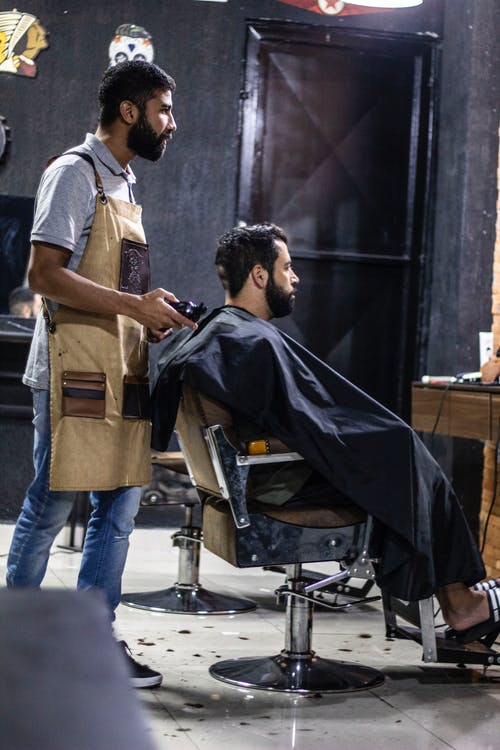 Man Wearing Brown Apron and Man Sitting on Gray Stainless Steel Barber's Chair
