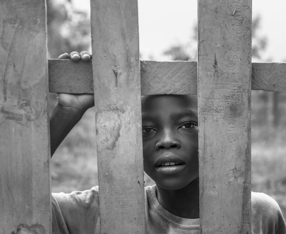 Grayscale Photo of Boy Standing Behind Wooden Fence