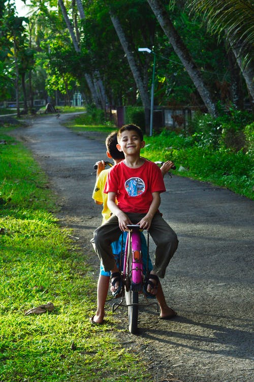 Boy Riding on Back of Bicycle