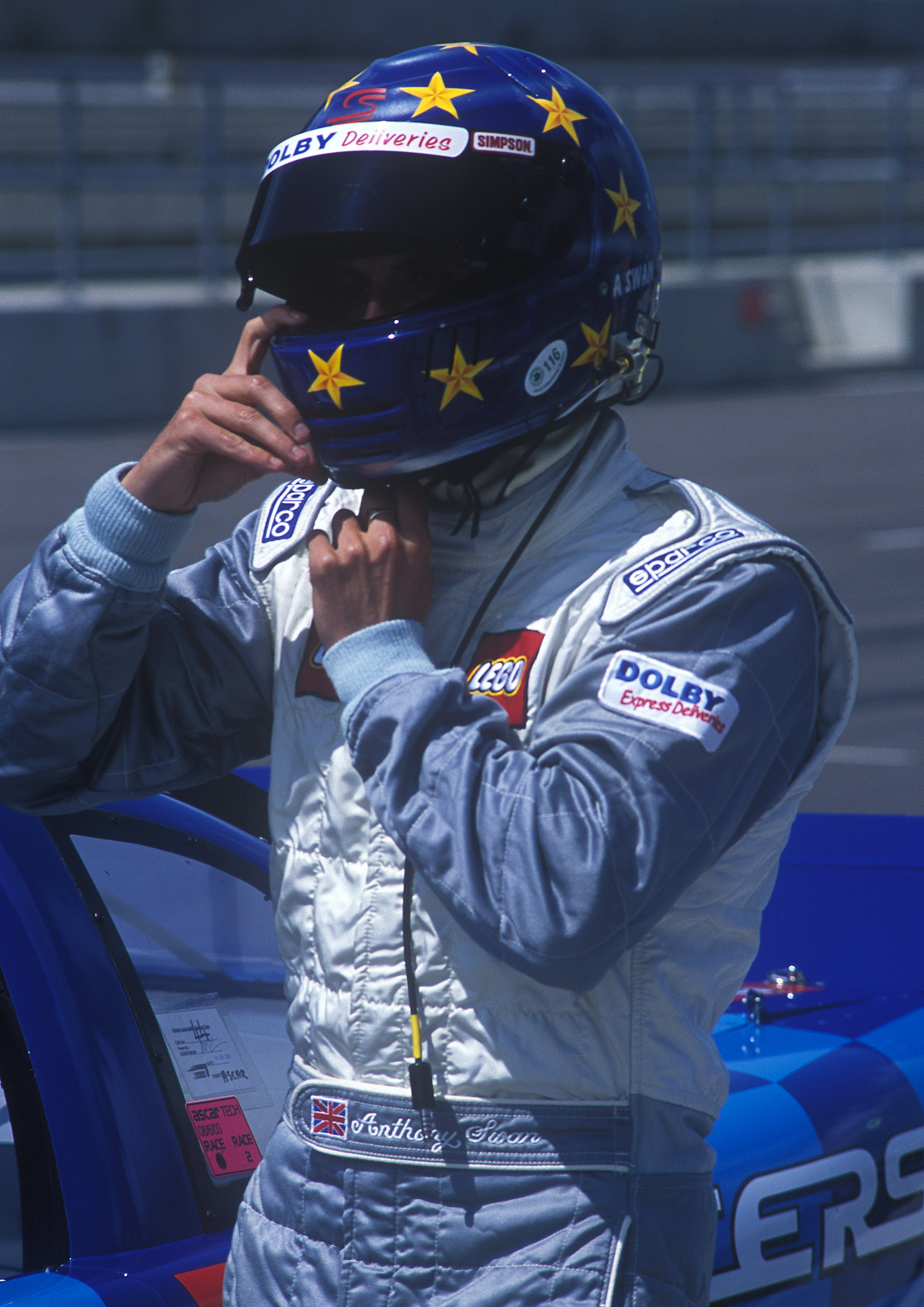 Man in Blue and and White Racer Suit Wearing His Blue and Yellow Star Full Face Helmet