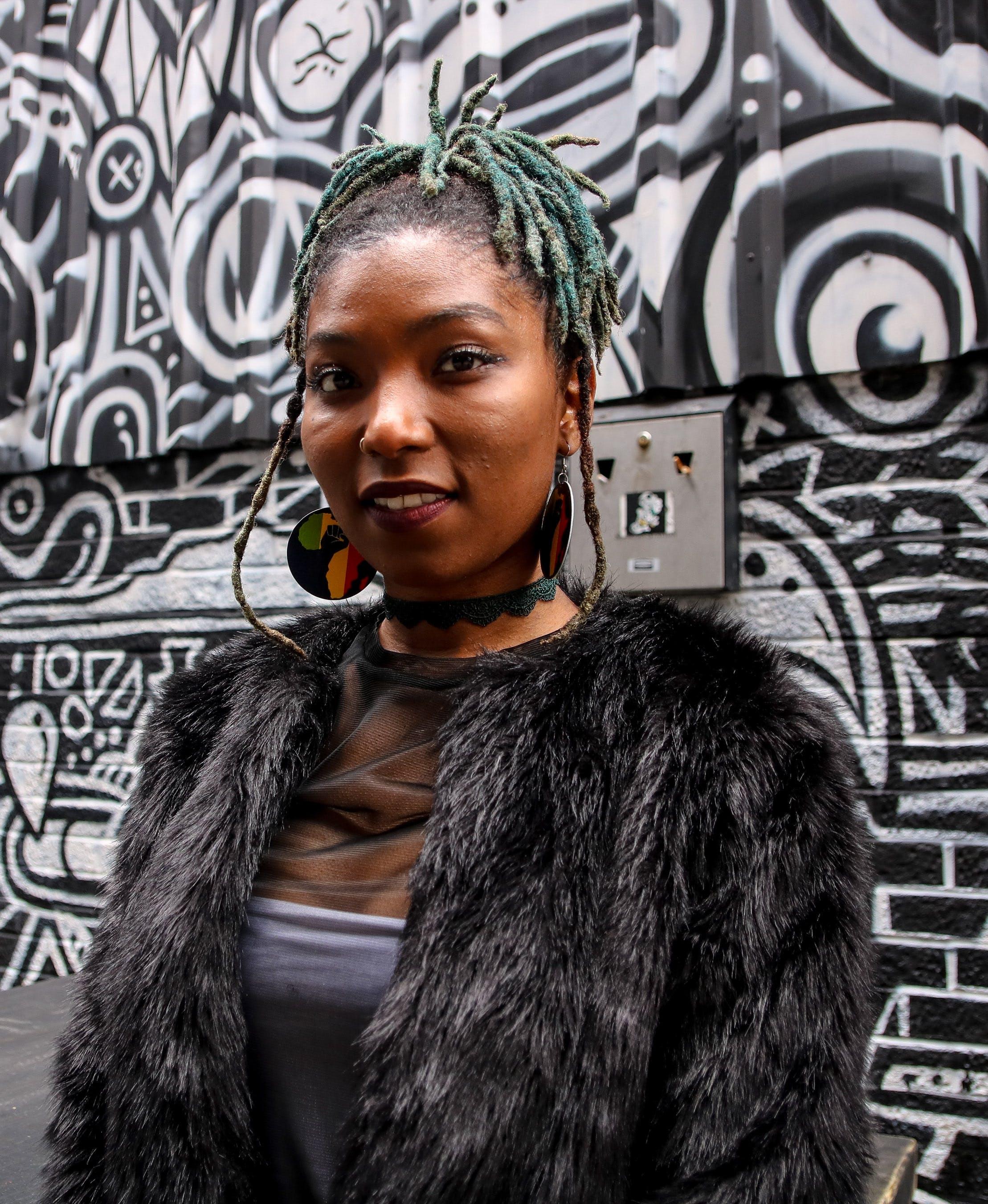 Portrait Photo of Woman in Black Faux Fur Coat Standing Next to Graffiti
