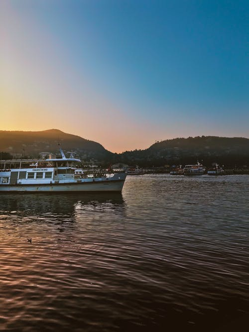 Foto d'estoc gratuïta de aigua, alba, barca, capvespre