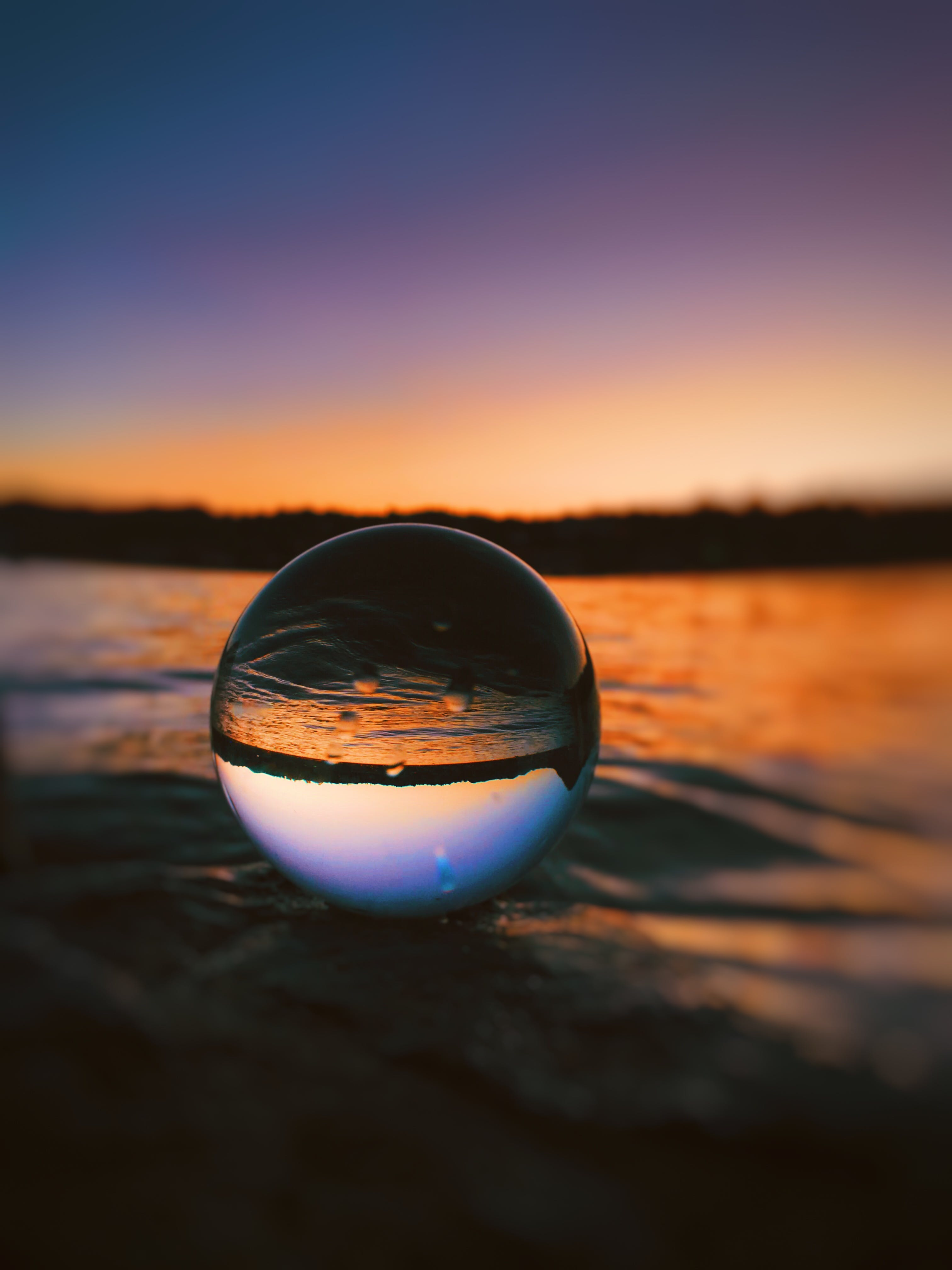 Clear Glass Ball on sand Surface
