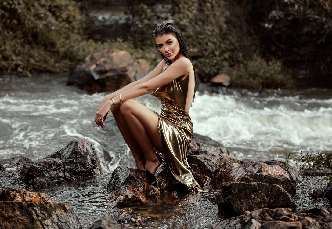 Woman in Gold Gown Sitting on Rock at the River