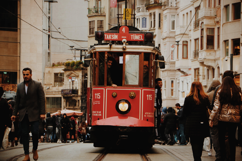 People Walking Beside Red Tram