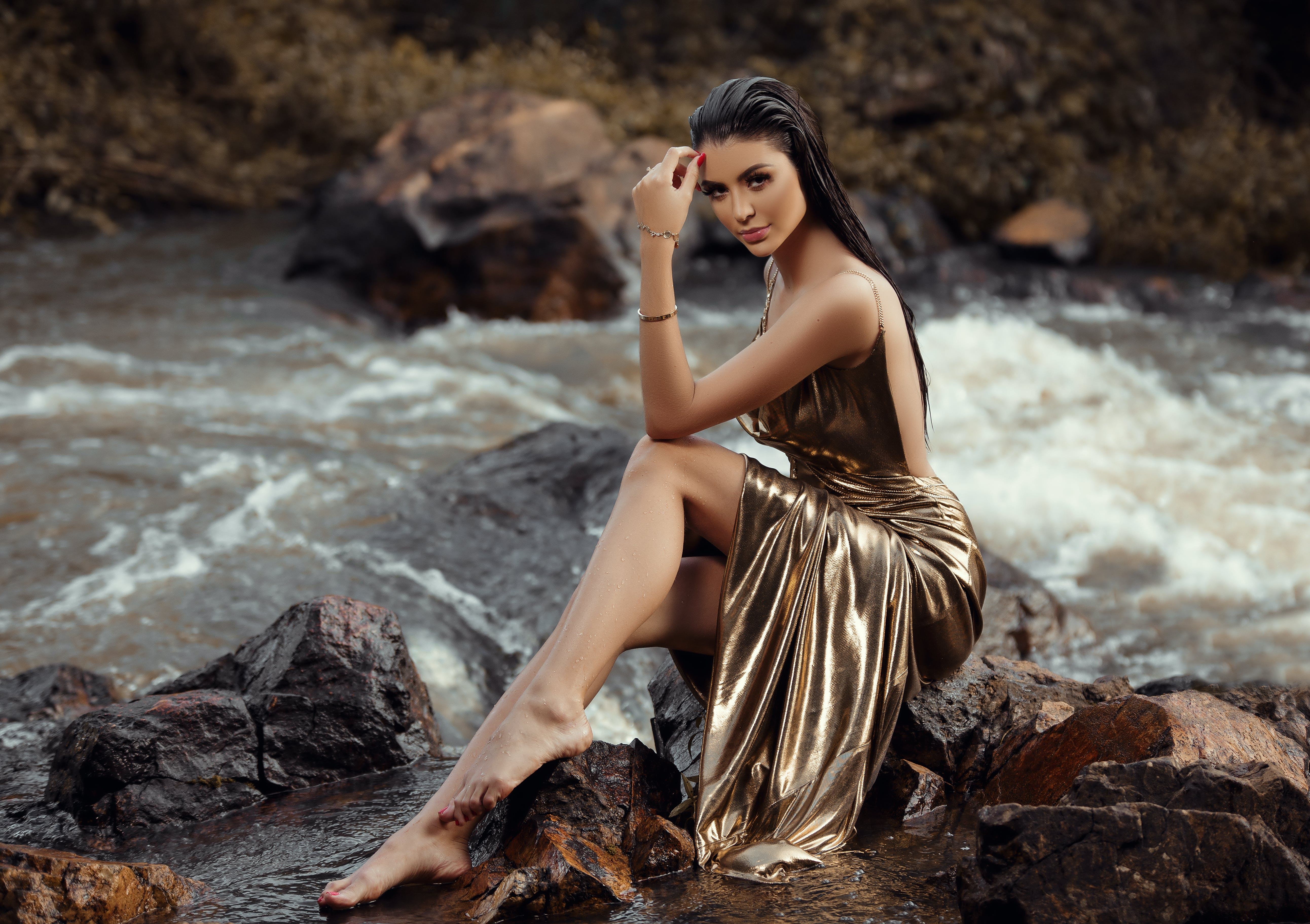 Photo of Woman in a Gold Gown Sitting on a Rock by the River