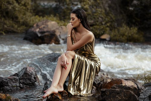 Woman Wearing Gold Silk Tube Dress Sitting Beside River