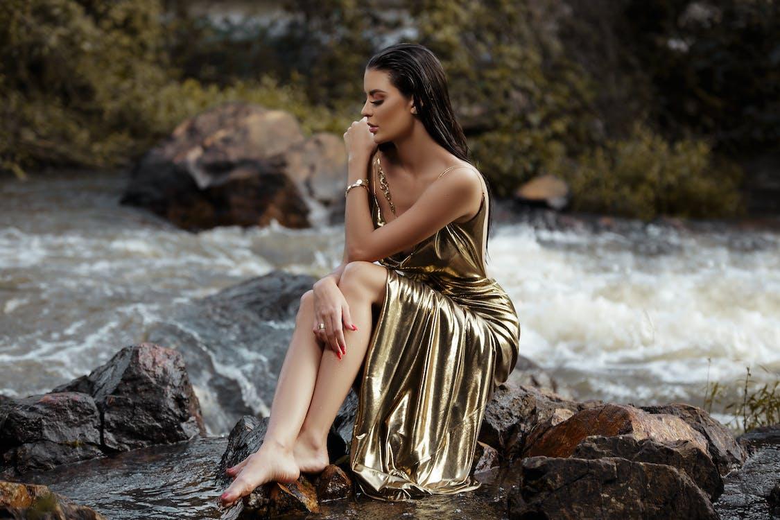 Woman Wearing Gold Silk Tube Dress Sitting Beside River