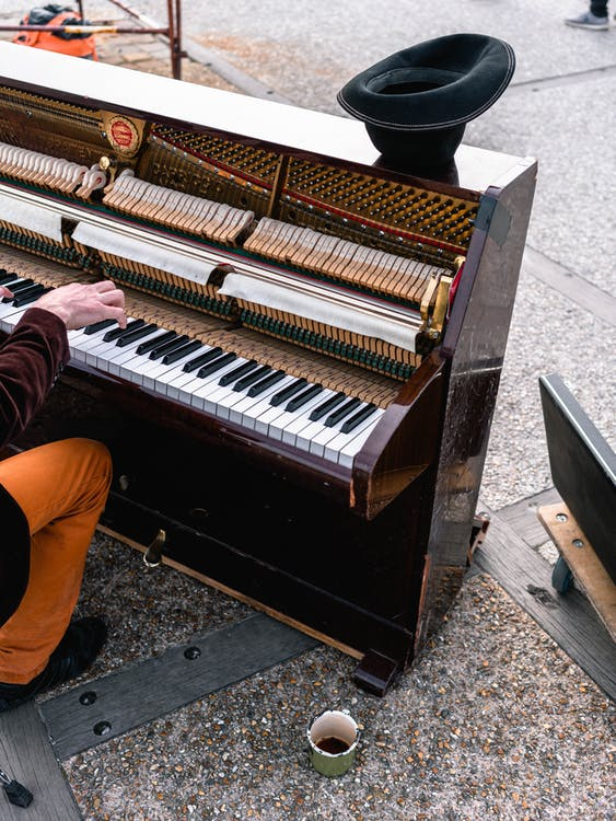Man Playing Brown Upright Piano