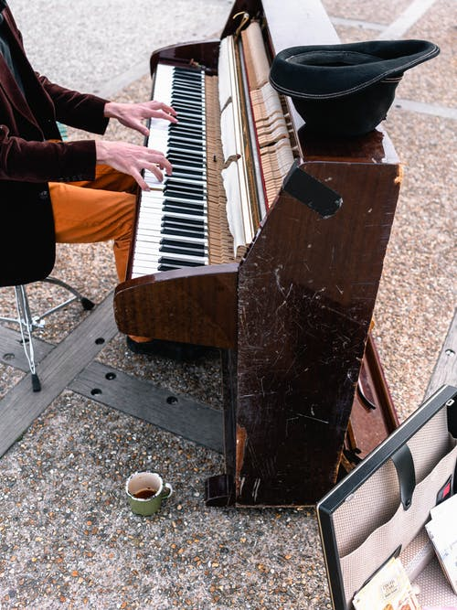 Man Playing Brown Upright Piano Outdoors