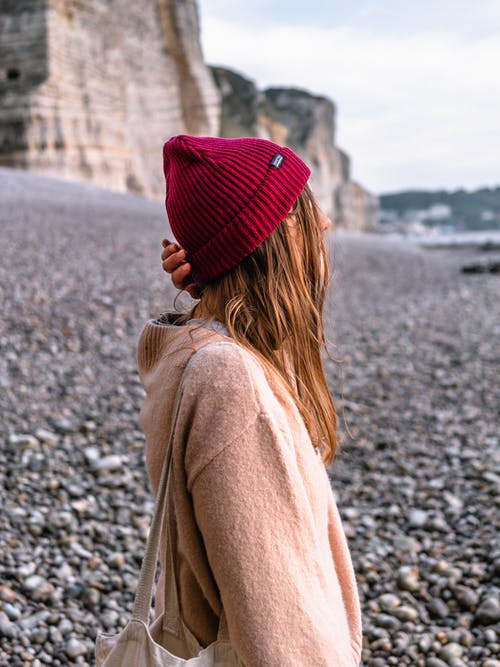Woman Wearing Pink Sweater and Red Knit Cap