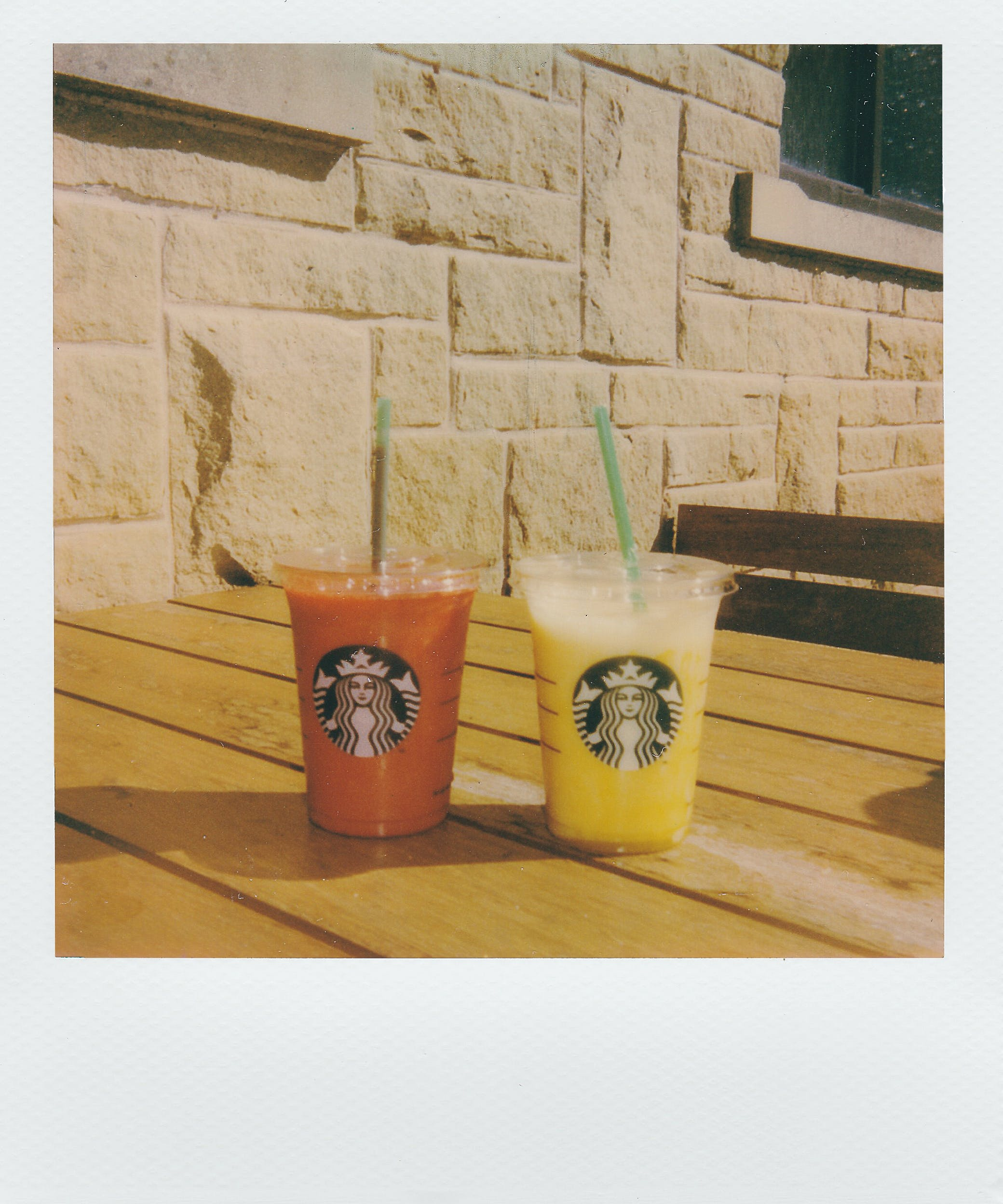 Two Orange and Yellow Starbucks Juices in Plastic Cups With Lids and Straws