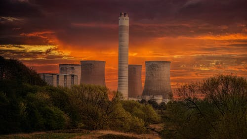 White Nuclear Plant Silo Under Orange Sky at Sunset