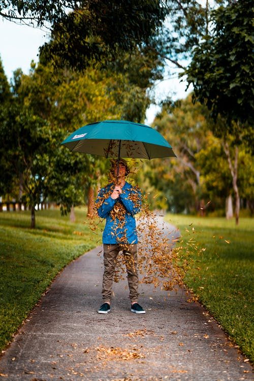 Man Standing and Using Blue Umbrella on Concrete Road Covered With Brown Leaves