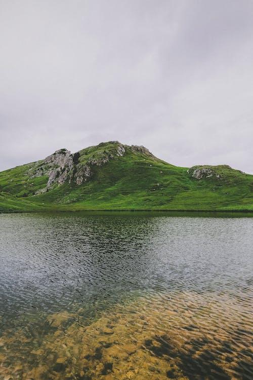 Body of Water Across Green Hill