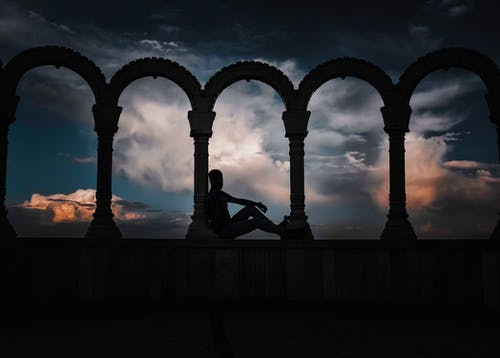 Silhouette Photo of Person Leaning on Arch Pillar