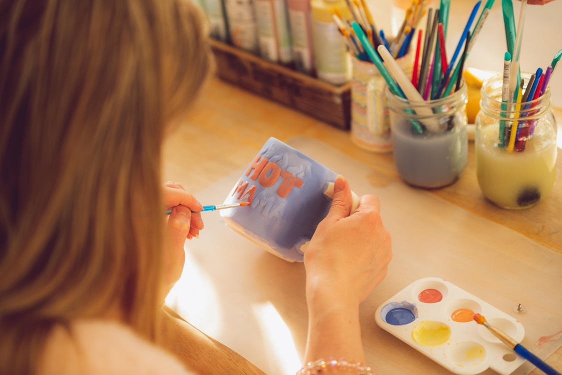 Person Painting on Mug