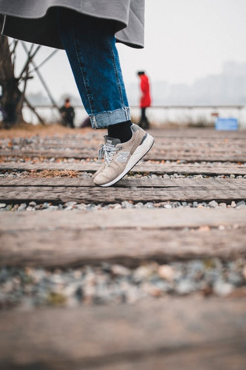 Selective Focus Photo of Person Standing on Wooden Planks