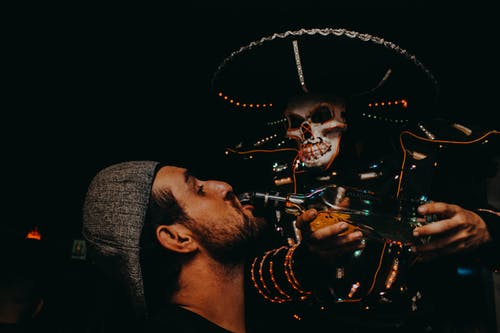 Skeleton Pouring Beverage on Man's Mouth