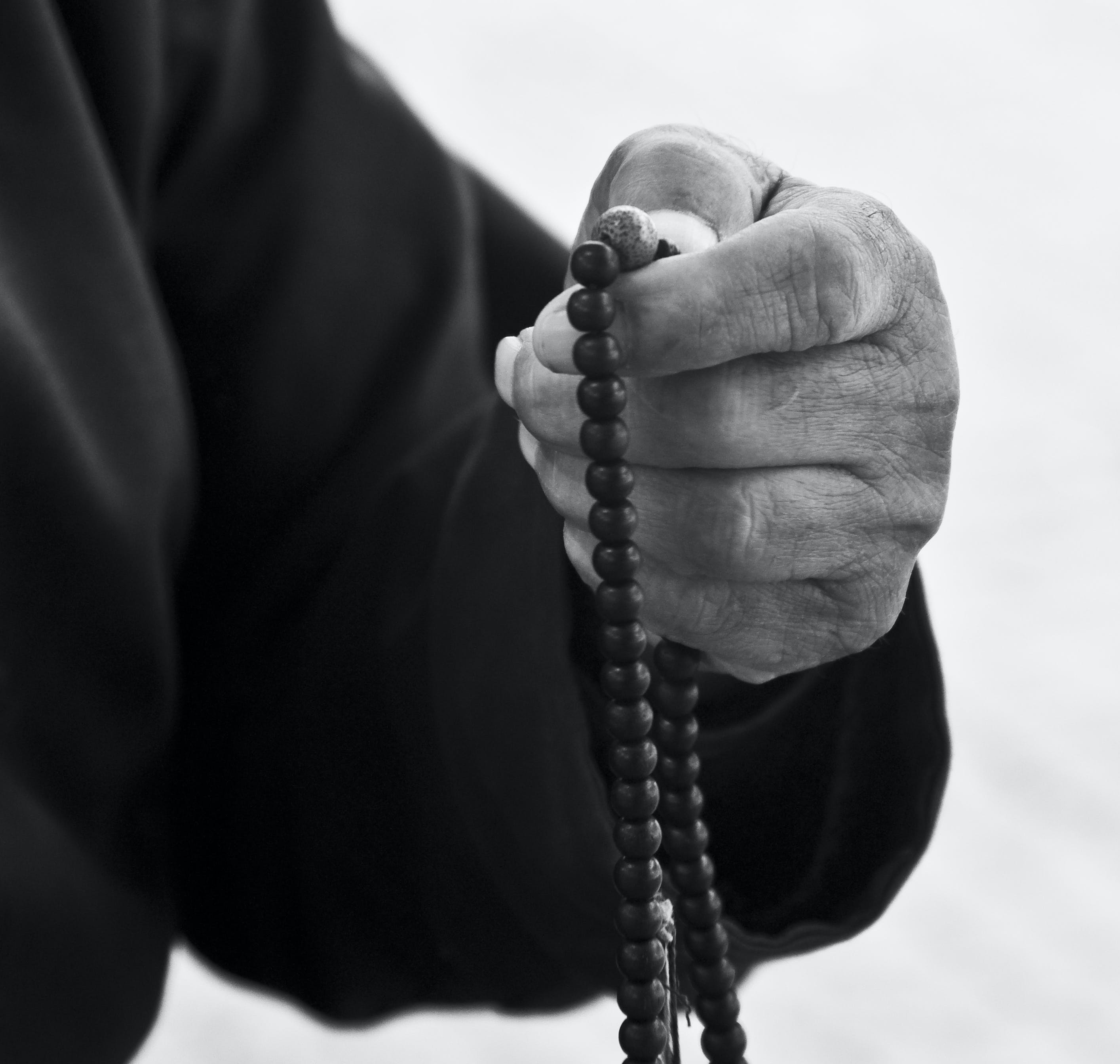 A person holding a beaded necklace
