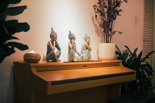 Three Buddha Sitting Figurines Near Oil Diffuser on Top of Piano