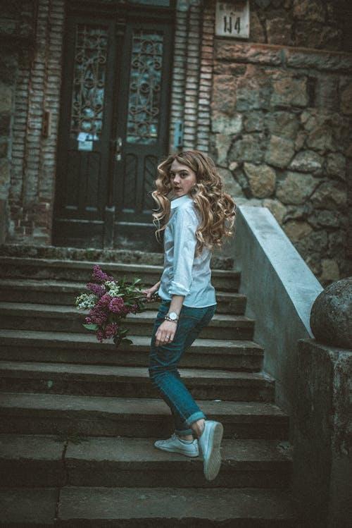 Foto profissional grátis de andando, ao ar livre, buquê de flores, cabelo ao vento