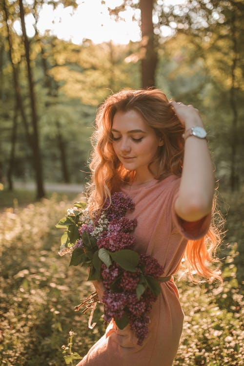 Woman Carrying Flowers While Walking Near Trees during Golden Hour
