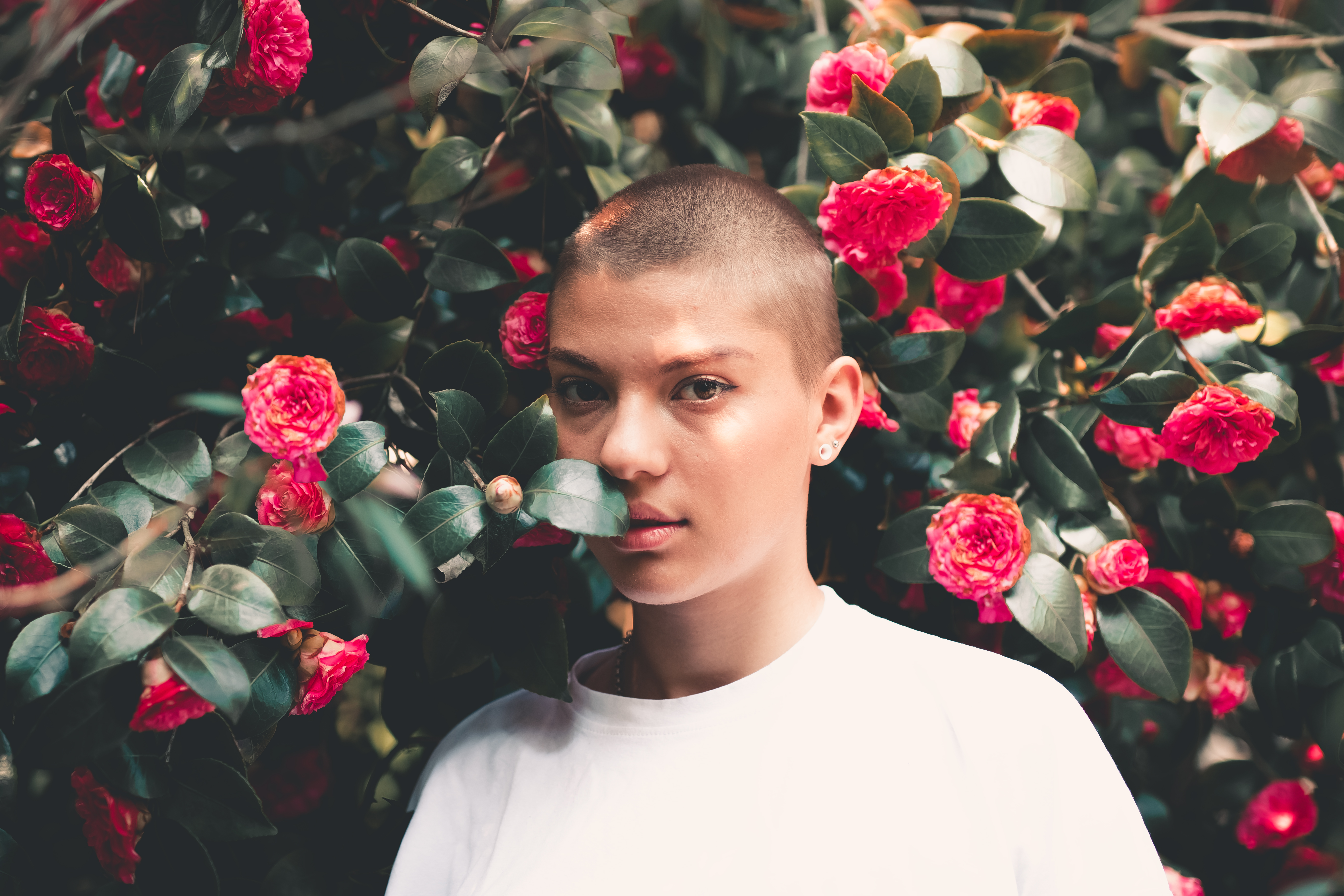 photo of bald woman in white t shirt standing beside red flowers