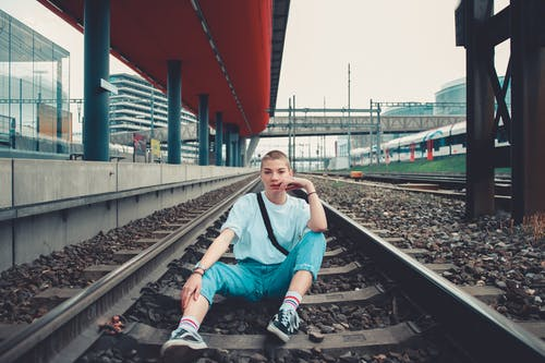 Person Sitting on Railway