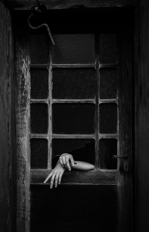Grayscale Photo of Person Leaning on Window