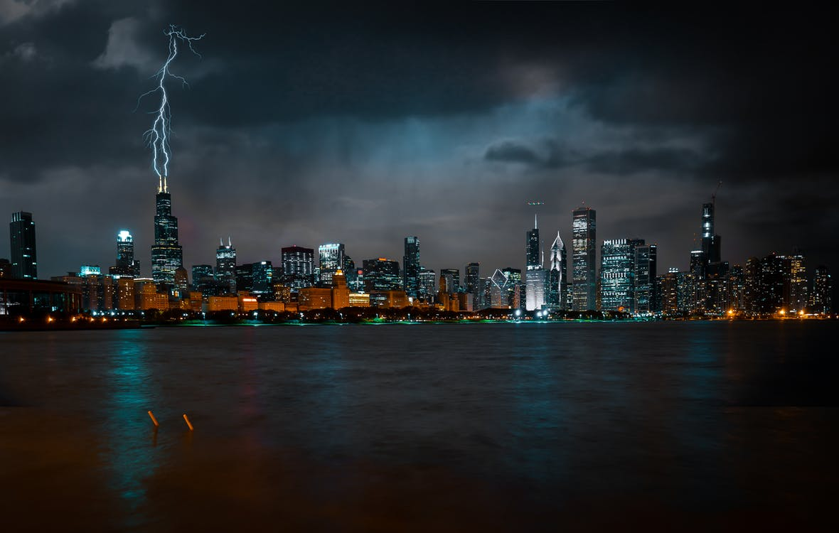 Photo of Chicago Cityscape at Night While Lightning Strikes High Rise Building