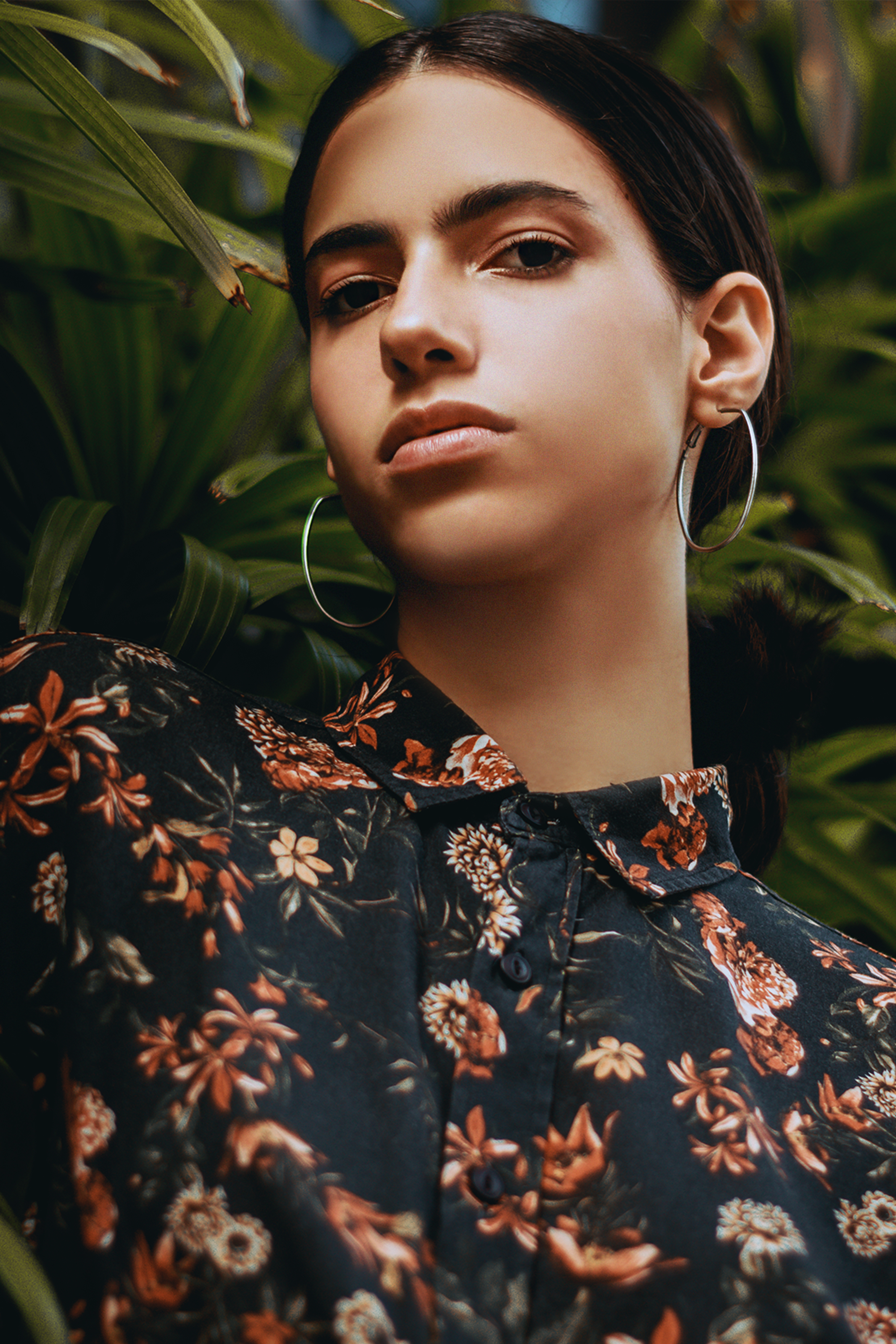 Woman Wearing Black and Multicolored Floral Blouse Near Green Leaf Plant