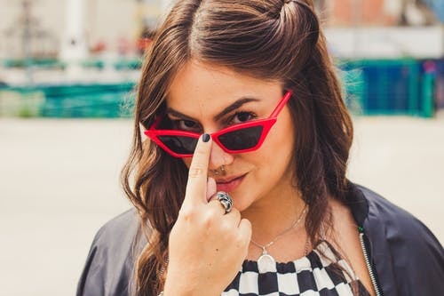 Selective Focus Portrait Photo of Woman Posing in Black Sunglasses With Red Frames